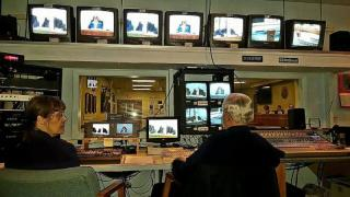 Volunteers sitting in chairs looking at television monitors and electronic equipment